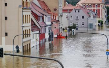Eine von Hochwasser überflutete Straße. Helfer retten Bewohner